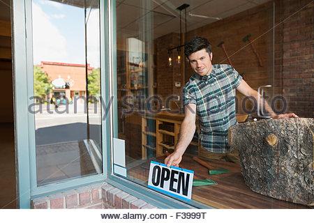 Portrait worker turning open sign in shop window - Stock Photo