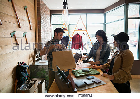Customer using credit card reader at shop counter - Stock Photo