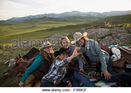 Female ranchers taking selfie in remote field - Stock Photo