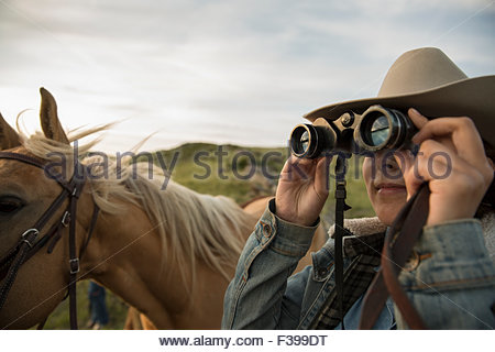 Female rancher with binoculars and horse - Stock Photo