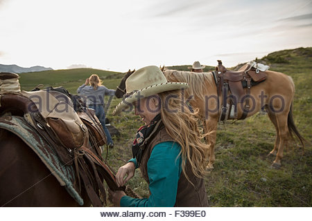 Female rancher adjusting saddle on horse in field - Stock Photo