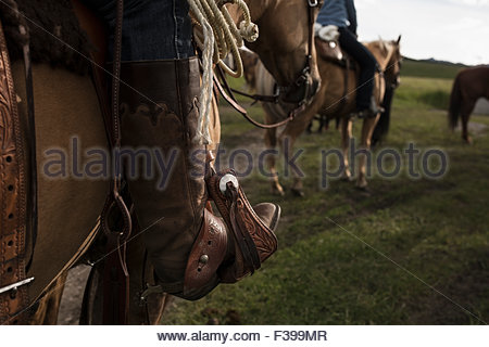 Close up of womans cowboy boot in stirrup, riding horse. - Stock Photo