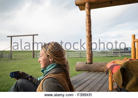 Pensive female rancher drinking coffee on porch - Stock Photo