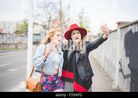 Knee figure of two young beautiful blonde and brunette girls having fun in the city taking selfie with smartphone - Stock Photo