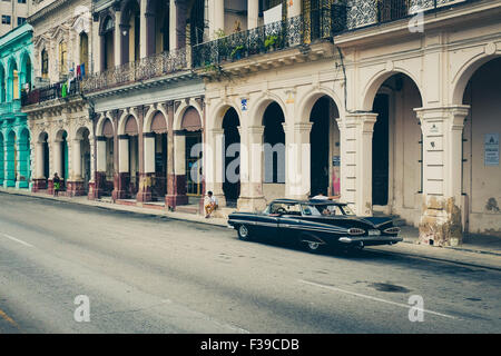 A vintage black Cuban car parked on The Prado in central Havana next to colonial buildings. Cuba. - Stock Photo