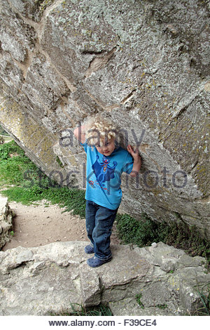 A four year old boy looks like he is holding up a tilting wall. - Stock Photo