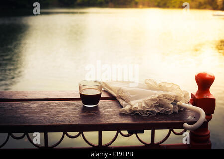 A glass of coffee and an umbrella on a wooden table by a lake in the afternoon - Stock Photo