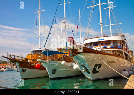 TROGIR, CROATIA -Touristic cruise ships are triple line moored on the quayside of Trogir sea promenade ready to - Stock Photo