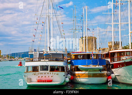 Trogir Croatia sea promenade with touristic cruise ships moored and Kamerlengo castle towers - Stock Photo