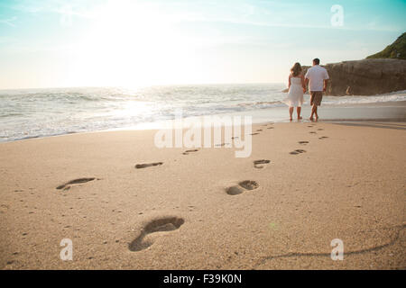 Rear view of a Young couple walking barefoot on the beach at sunset, Laguna Beach, Orange County, California, USA - Stock Photo