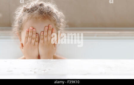 Portrait of a girl sitting in a bath covering face with her hands - Stock Photo