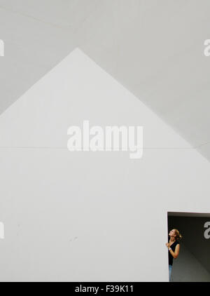 Woman looking up through a door - Stock Photo