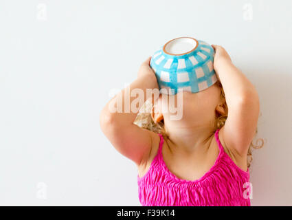 Girl with her head back holding cereal bowl to her mouth - Stock Photo