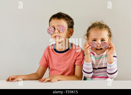 Boy and girl wearing sunglasses made of cookies covered in sprinkles - Stock Photo