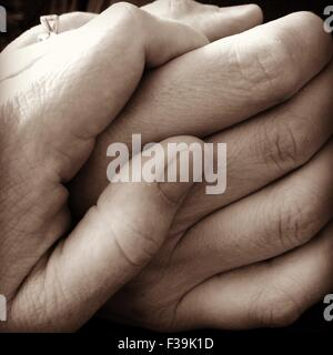 Close up of a couple holding hands - Stock Photo