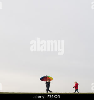 Boys walking, holding an umbrella - Stock Photo