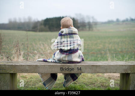 Rear view of a boy sitting on bench, wrapped in warm blanket - Stock Photo