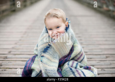 Portrait of a boy wrapped in blanket, sitting on a wooden bridge - Stock Photo