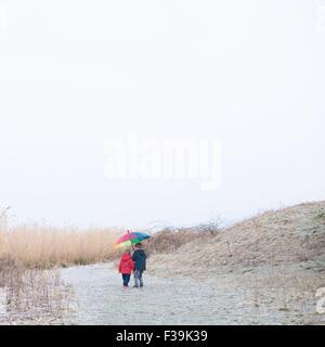 Two boys walking on beach with a multi coloured umbrella - Stock Photo