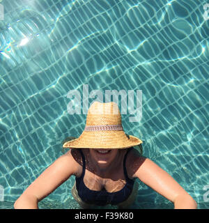 Smiling woman standing in a swimming pool with a straw hat covering her face, Thailand - Stock Photo