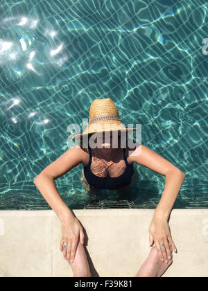 Woman standing in swimming pool touching a man's feet - Stock Photo