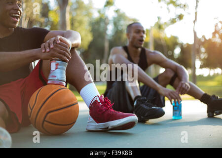 Two young men taking a water break while playing basketball in the park at sunset - Stock Photo