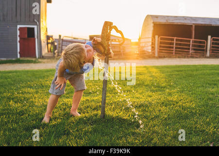 Boy drinking water from tap on a farm - Stock Photo