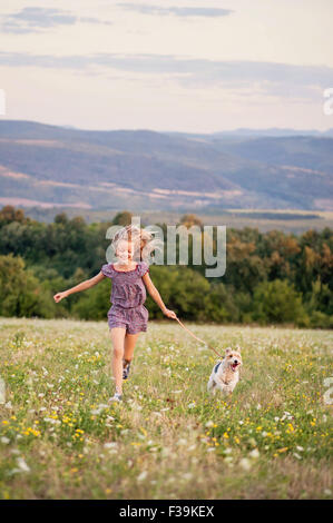 Portrait of a girl running with her fox terrier dog in a field - Stock Photo
