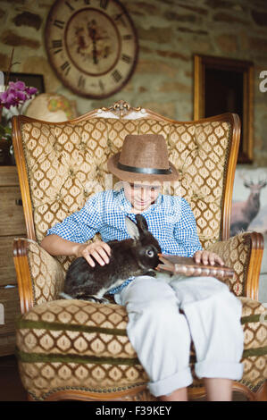 Boy sitting with his pet rabbit while holding a book - Stock Photo