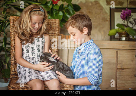 Boy and girl playing with their pet rabbit - Stock Photo