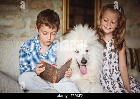 Boy and girl reading a book with their pet poodle dog - Stock Photo
