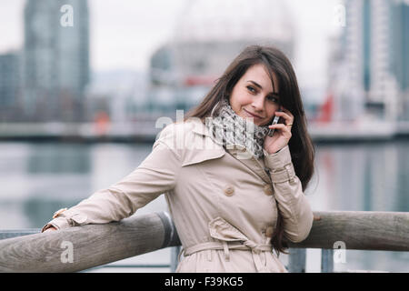 Portrait of a smiling woman talking on mobile phone - Stock Photo