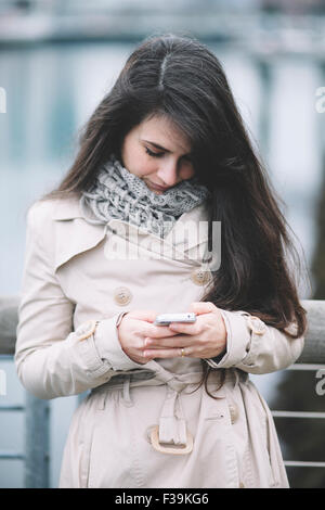 Portrait of a woman texting on her mobile phone - Stock Photo
