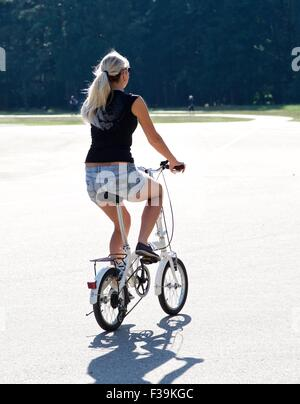 Rear view of a woman riding bicycle in the park, Lithuania - Stock Photo