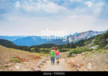 Rear view of Boy and girl  walking along a path with their arms around each other - Stock Photo