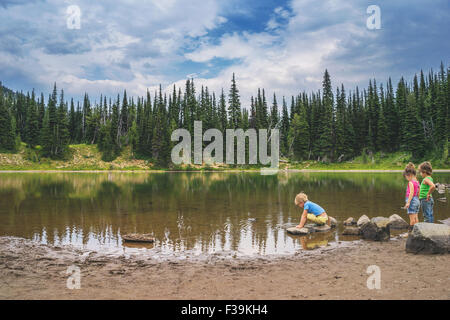 Three children playing by a lake - Stock Photo