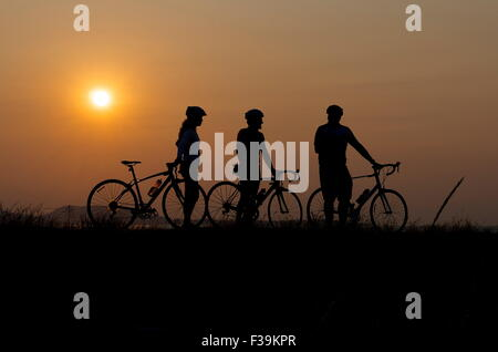 Silhouette of three cyclists at sunset - Stock Photo