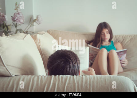 Teenage boy and girl sitting in the sofa reading books - Stock Photo