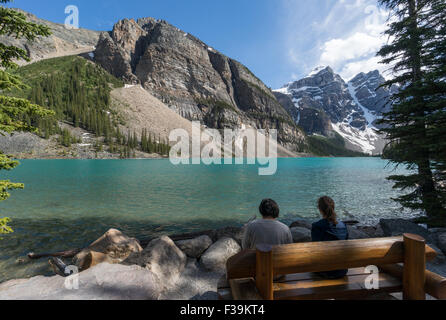 Two people sitting by Moraine Lake, Banff National Park, Canadian Rockies, Alberta, Canada - Stock Photo