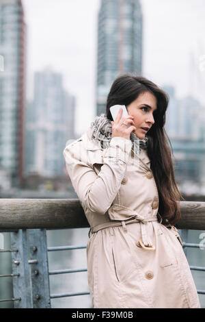 Portrait of a woman standing on a balcony talking on her mobile phone - Stock Photo