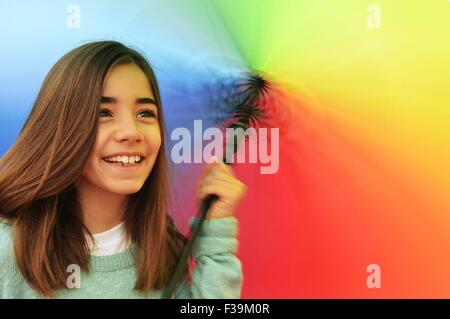 Portrait of a smiling girl twirling a multi-colored umbrella - Stock Photo