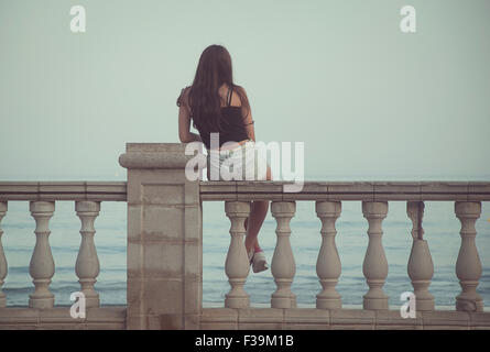 Rear view of a teenage girl sitting on a wall overlooking the sea - Stock Photo