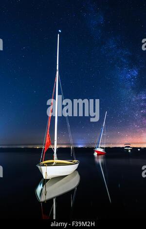 Three sailing boats anchored at night - Stock Photo