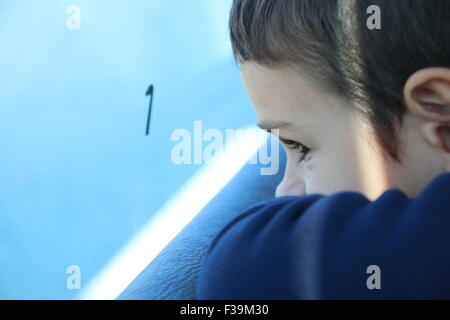 Close-up portrait of a boy looking out of a window on a train journey - Stock Photo
