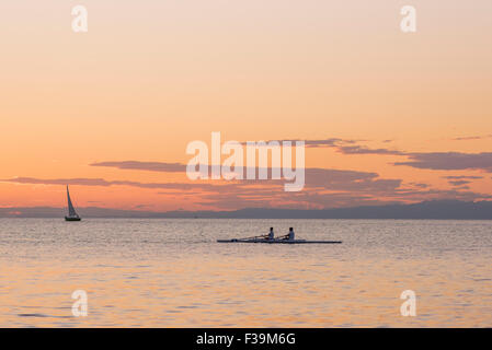 People rowing sunset, at sunset a rowing team practise in Trieste harbour, Italy. - Stock Photo