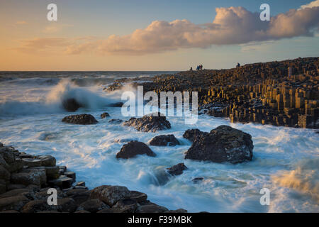 Tourist watching the setting sun on the Giant's Causeway, County Antrim, Northern Ireland - Stock Photo