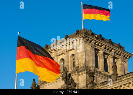 Two german flags waving on one of the corners of the Reichstag in Berlin - Stock Photo