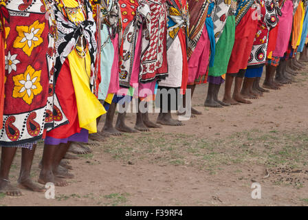 A line of barefoot Masai Women wearing the traditional shawls called Kangas, in a village near the Masai Mara, East - Stock Photo