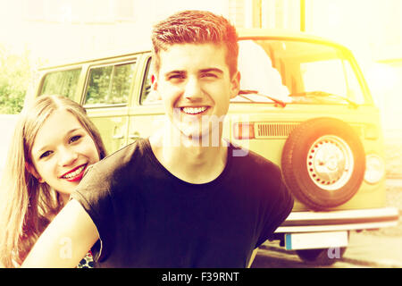 Young happy couple with old bus - Stock Photo