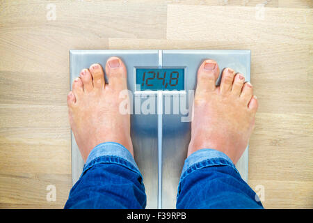 Man standing on weight scales with bare foot - view from top - Stock Photo